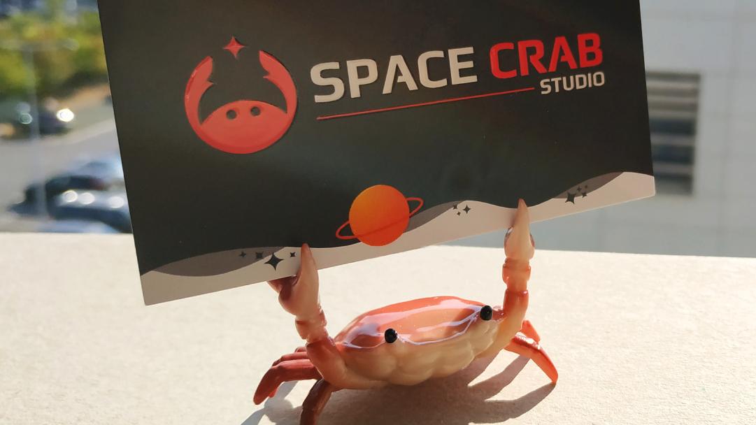 Crabby tiens la carte de visite de Space Crab Studio Agence de communication à Reims